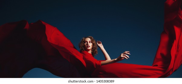 woman dancing in silk dress, artistic red blowing gown waving and flittering fabric in the night