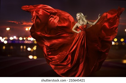 woman dancing in silk dress, artistic red blowing gown waving and flittering fabric, night city street lights