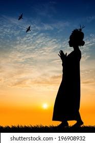 Woman dancing Thai dance at sunset