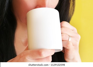 Woman with dark black hair and wedding ring is holding mug in two hands and drinking coffee or tea. Mug mockup for woman's gift