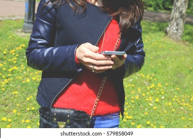 A woman in a dark blue jacket with a mobile phone in hands on a walk in a sunny spring park. Girl with cell. Spring casual outfit