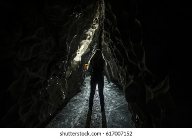 Woman in the dark cave with flaslight. back view. scenist girl between stones wall.