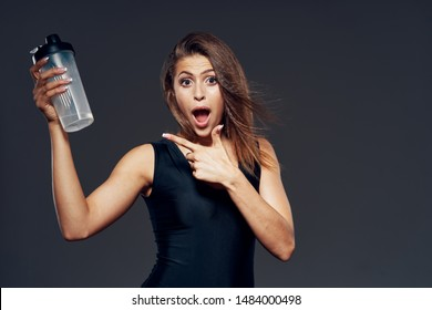 A woman in dark clothes points a finger at a bottle of water and opened her mouth wide