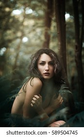 Woman in a dark forest looking into camera