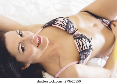 Woman with dark hair in pink and black sexy underwear with white background