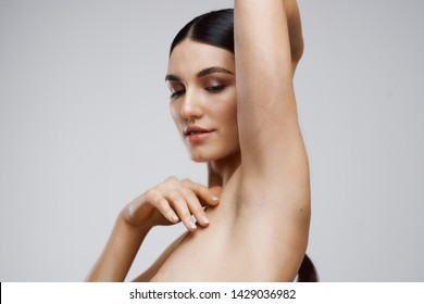 a woman with dark hair shows the underarms and clean skin SPA procedures salon