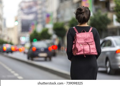 Woman with dark hair standing in the street waiting for someone. Fashionable young lady walking down the street. Modeling a metallic pink backpack and sporting a fun hair bun.