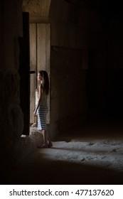 woman in the dark side of huge wooden door