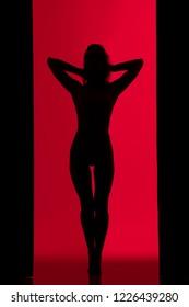Woman dark silhouette dancing against red wall