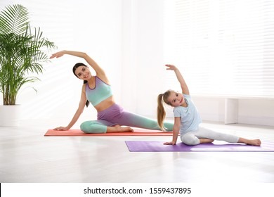 Woman and daughter doing yoga together at home. Fitness lifestyle
