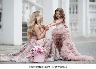 woman with daughter in fashionable dresses. girl bride with child posing outdoors