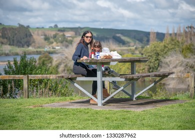 Woman with daughter relaxing for a picnic on a park bench table.