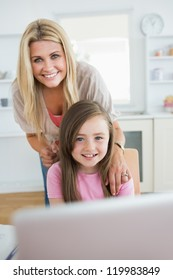 Woman and daughter smiling at the laptop in the kitchen