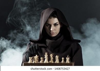 woman in death costume playing chess in smoke on black