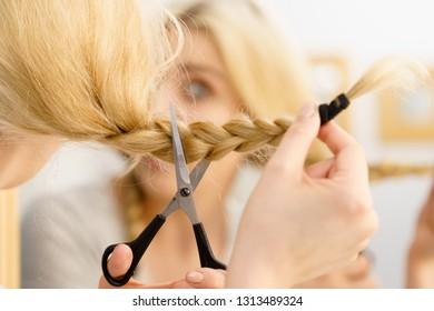 Woman deciding to cut her long blonde hair tied in braid. Hairstyle change at home.