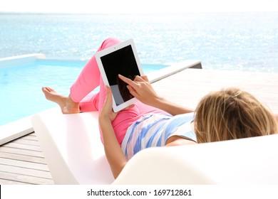 Woman in deckchair using digital tablet