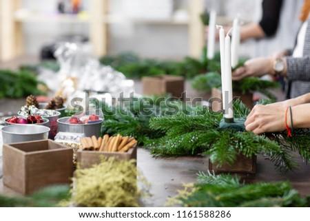 A Christmas Arrangement.Woman Decorates Christmas Arrangement Candles Hands Stock