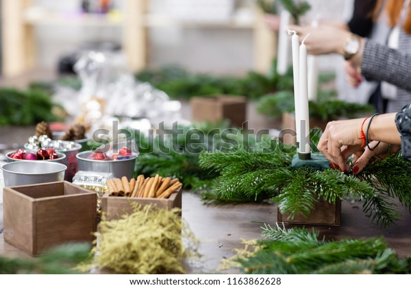 A woman decorates a Christmas arrangement with candles. Hands close-up. Master class on making decorative ornaments. Christmas decor with their own hands. The new year celebration. Flower shop