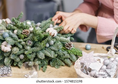 A woman decorates a Christmas arrangement. Hands close-up. Master class on making decorative ornaments. Christmas decor with their own hands. The new year celebration. Flower shop