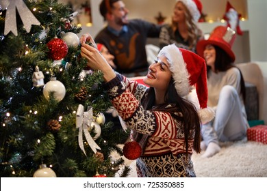 Woman decorates Christmas tree on New years eve at home