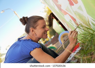 Woman decorates the walls of buildings