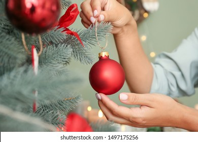 Woman decorating beautiful Christmas tree at home, closeup