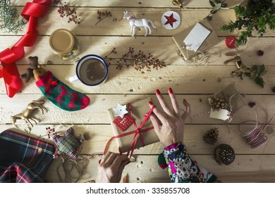 woman decorating a Christmas present with a branch of holly, Do-it-yourself Christmas decoration
