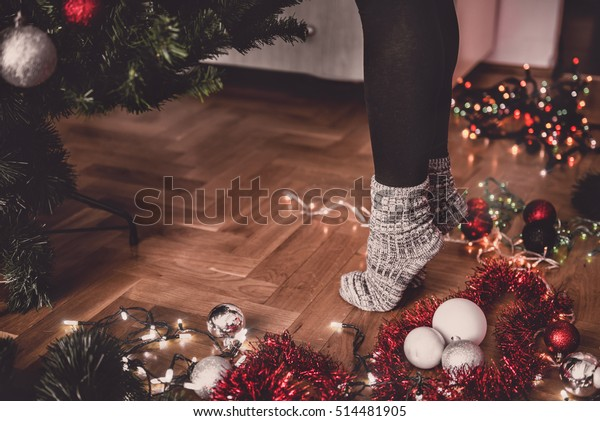 Woman decorating a christmas tree and standing tiptoe