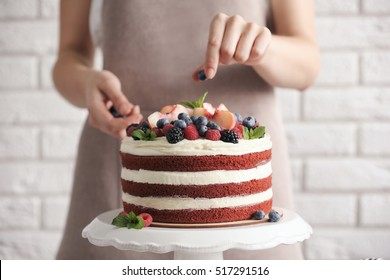 Woman decorating delicious cake