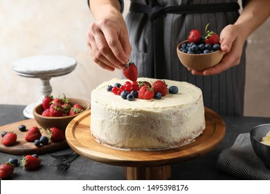 Woman decorating delicious homemade cake with fresh berries at table indoors, closeup