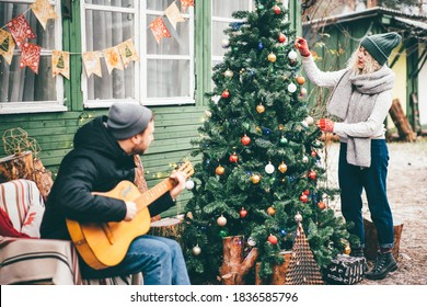 Woman decorating home for Christmas and hanging baubles on Christmas tree while her boyfriend playing guitar at the backyard.
