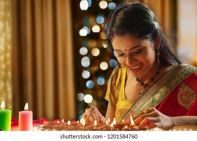 Woman decorating the house with diya on the occasion of Diwali