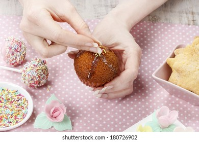 Woman decorating muffins