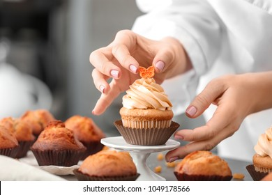 Woman decorating tasty cupcake at table