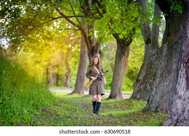 woman the defender, costs with automatic machine in the wood at sunset