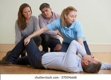 Woman Demonstrating Recovery Position In First Aid Training Class