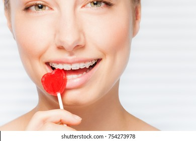 Woman with dental braces biting red lollipop