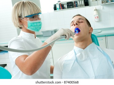 woman dentist with mask working on male patient teeth