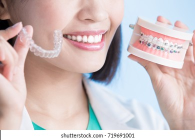 woman dentist take brace on the blue background