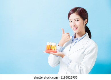woman dentist take implant tooth and thumb up on the blue background