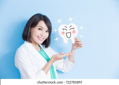 woman dentist take tooth board and show something on the blue background