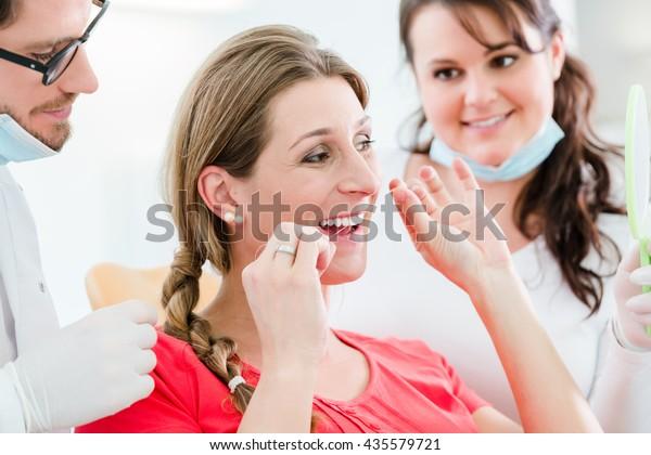 Woman at dentist using dental floss, the doctor explaining proper use