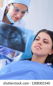 Woman dentist working at her patients teeth . Woman dentist looking at x-ray