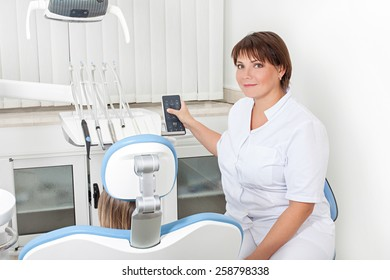 woman dentist in the workplace regulates the chair with the patient