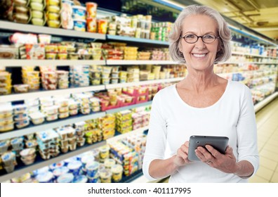 Woman in departmental store choosing items from tablet pc
