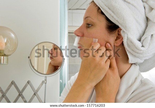 A woman is depilating the small hairs from her moustache in front of a mirror