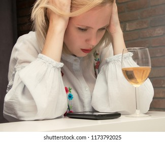 A woman in depression, feeling unwell before the phone and a glass of wine. The concept of female alcoholism.