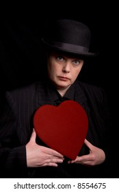 Woman in a derby and suit holding a red candy heart box