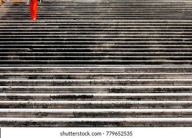 A woman descends the long stairs in Rome