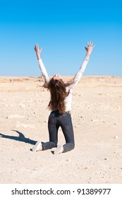 woman in desert with her hands up